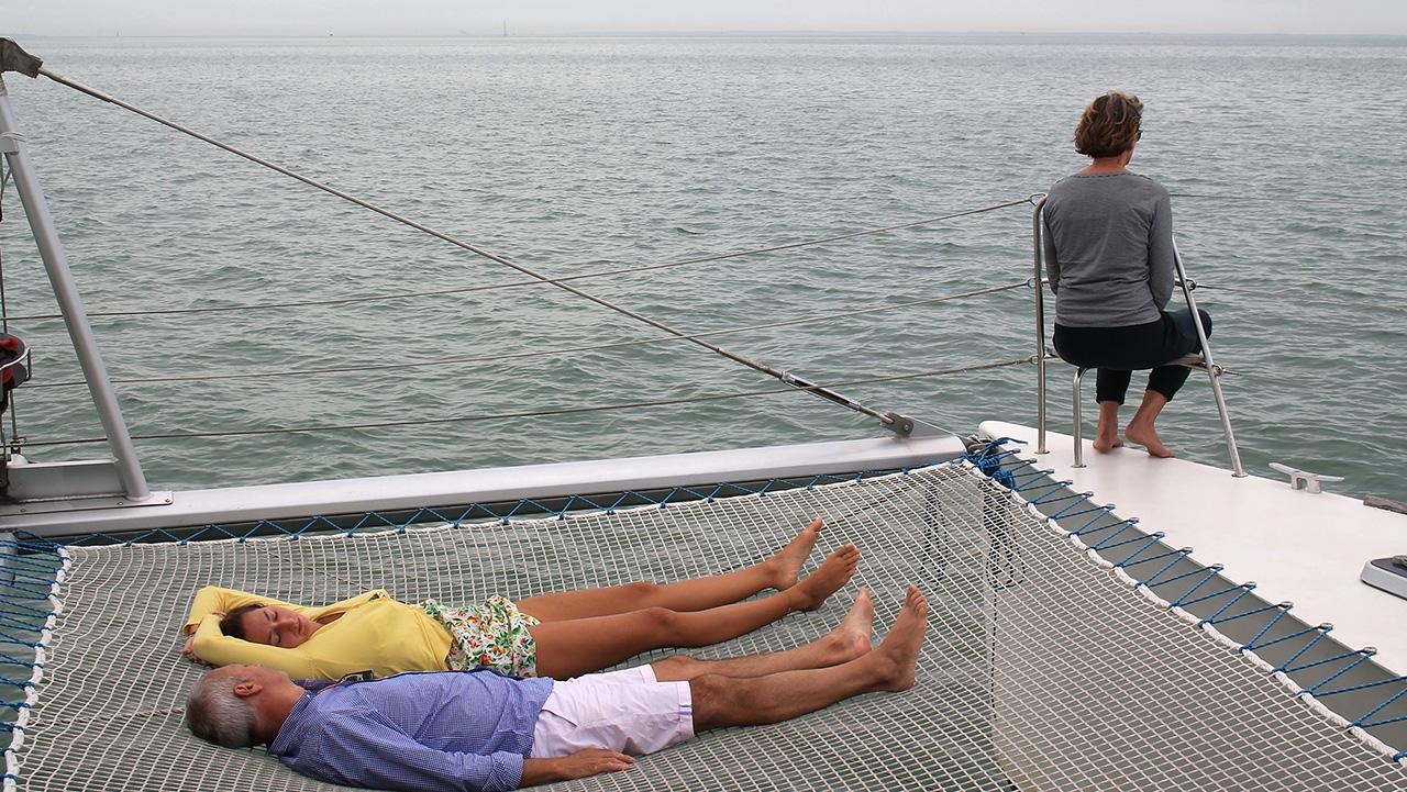 Détente en mer à bord du ctamaran kapalouest, sur les trampolines